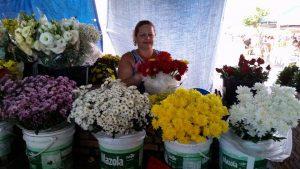 Descrição da imagem. Foto horizontal de vários baldes brancos grandes com diversas flores dentro, cada balde com um tipo e cor de flor. Ao centro, uma mulher sorridente segura um buquê de flores vermelhas. Fim da descrição.