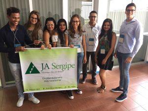 Descrição da imagem. Foto horizontal de um grupo de oito jovens de pé, sorridentes, usando crachá, e os cinco do lado esquerdo seguram juntos um banner branco e verde com o nome JA Sergipe. Fim da descrição.