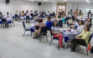 Descrição da imagem. Foto horizontal de um salão amplo, branco, com várias mesas forradas de branco e cadeiras azuis com pessoas setadas nas mesmas. Fim da descrição.