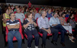 Descrição da imagem. Foto horizontal de uma plateia lotada de pessoas sentadas e apenas um rapaz em pé no fundo. As cadeiras são acolchoadas de cor vermelha, o piso é de carpete cinza e o ambiente tem pouca iluminação. Fim da descrição.