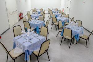 Descrição da imagem. Foto horizontal de um salão retangular comprido com duas filas na vertical de quatro mesas cada, forradas com toalhas azuis e brancas sobrepostas. Em cada mesa, quatro cadeiras acolchoadas na cor bege. À frente de cada cadeira, sobre as mesas,  uma taça transparente com guardanapo de tecido dobrado e colocado sobre as mesmas, dois pares de talheres prateados. O piso e as paredes são brancos. Fim da descrição.