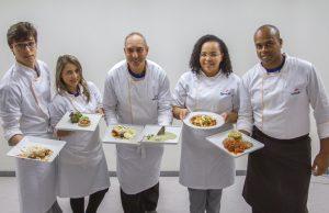 Descrição da imagem. Foto horizontal de cinco pessoas de pé, de frente, olhando para a câmera, vestindo avental branco de cozinheiro com logomarca do Senac