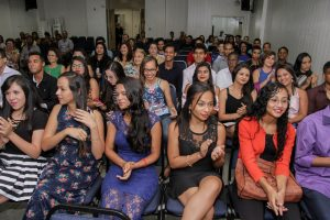Descrição da imagem. Foto horizontal de uma plateia repleta de pessoas jovens. Fim da descrição.